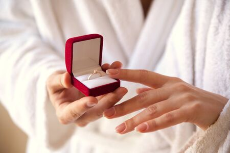Photo pour Marriage proposal. The hand holds a red gift box with a gold ring. Sentence. The best day. Gives a ring. A touch of hands. Engagement. Closeup - image libre de droit