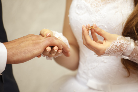Foto de Wedding day. Ceremony. Wedding hands with rings. The bride's hand wears an engagement ring on the finger of the groom. Close up - Imagen libre de derechos