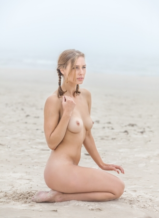 Photo for Young nude woman on sandy beach at foggy day - Royalty Free Image