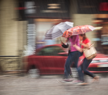 People walking down the street in rainy day. Intentional motion blur