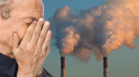 Foto de Ecological concept. Elderly man with a face closed by hands against the background of pipes polluting an atmosphere - Imagen libre de derechos