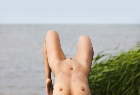 Beautiful young nude woman on nature background