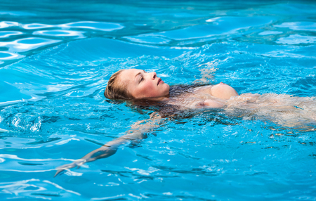 Photo for Young naked woman enjoy swimming in the pool - Royalty Free Image