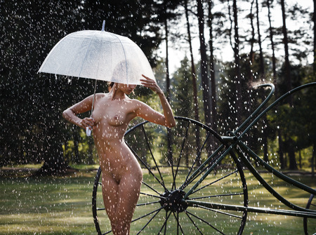 Foto für Nude woman outdoors enjoy nature. Young beautiful naked woman with an umbrella on nature under a summer rain and in the rays of sunlight - Lizenzfreies Bild