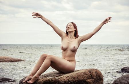 Photo for Beautiful girl enjoying nature. Nude woman posing on sea beach - Royalty Free Image