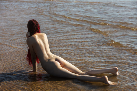 Photo pour Beautiful girl outdoors enjoying nature. Young naked woman with scarlet dreadlocks enjoys the sea on the coast - image libre de droit