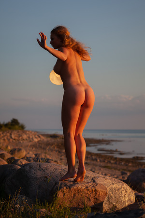 Photo for Young nude woman with a white hat standing on a stone by the sea in the rays of the sunset sun. View from the back - Royalty Free Image