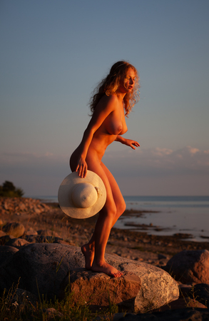Foto per Young nude woman with a white hat standing on a stone by the sea in the rays of the sunset sun - Immagine Royalty Free