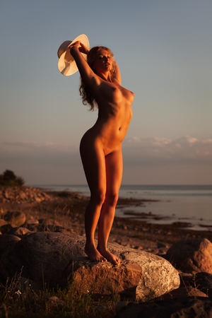 Photo for Young nude woman with a white hat standing on a stone by the sea in the rays of the sunset sun - Royalty Free Image