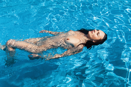 Foto de Beauty and healthy lifestyle concept. Beautiful young nude woman in swimming pool. Young naked woman enjoy swimming in the pool - Imagen libre de derechos