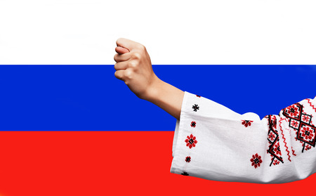 Foto de Political metaphor. Russian Ukrainian conflict. Female hand in the Ukrainian national costume showing the fig against the background of the Russian flag - Imagen libre de derechos