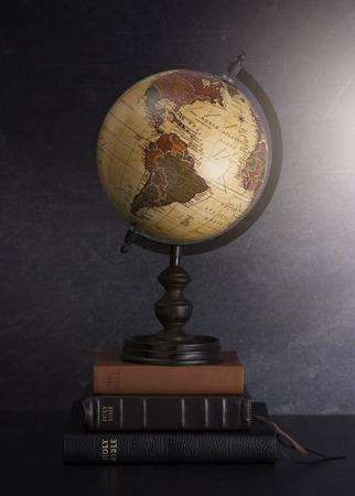 Photo pour Stack of Bibles and a Globe on a Dark Background - image libre de droit