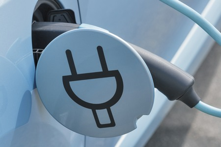 Photo pour Charging an electric car with the power cable supply plugged in, closeup - image libre de droit