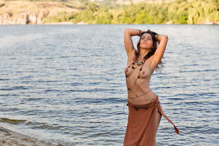 Foto de young caucasian beautiful naked Amazon woman on the sand river beach - Imagen libre de derechos