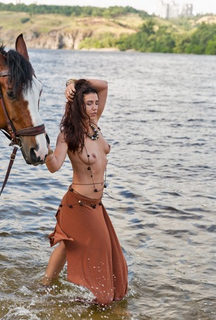 Photo pour young caucasian beautiful naked Amazon woman on the river shore with red horse - image libre de droit