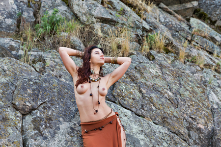 Foto per young caucasian beautiful naked Amazon woman stands in front of rocks - Immagine Royalty Free
