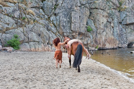 Foto de young white man in loincloth taken captive by the young caucasian beautiful naked Amazon woman on red horse. the sand river beach with mountain in background - Imagen libre de derechos