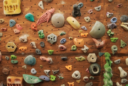 homemade artificial climbing wall covered with colored holds for rock climbing training
