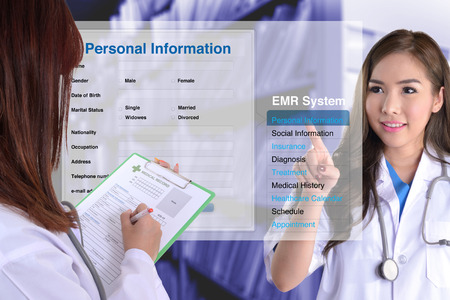 Foto de Female doctor show how to use electronic medical record while another one checking patient information by hand. - Imagen libre de derechos