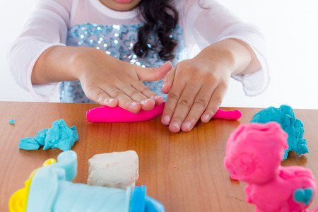 Photo pour Little girl is learning to use colorful play dough on white background - image libre de droit