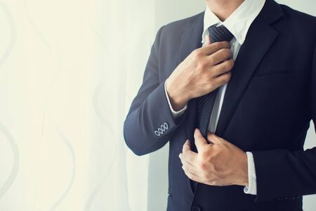 Photo pour People, business,fashion and clothing concept - close up of man in shirt dressing up and adjusting tie on neck at home. - image libre de droit
