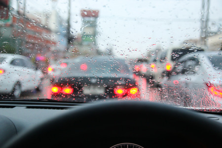 Driving on a rainy in a city, view from inside.