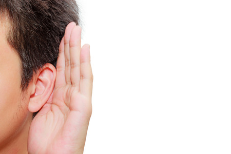 Foto de Asian man holds his hand near his ear and listening - Imagen libre de derechos