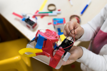 Foto de Robot from trash, STEAM activity for students, Plastic box with paper strips, DC motor and two AA batteries, colored tapes. Tinkering and making, educational activities for schools and children - Imagen libre de derechos