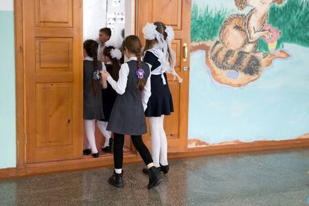 Foto de Two schoolgirls look at the door of the classroom, standing in the school corridor. - Imagen libre de derechos