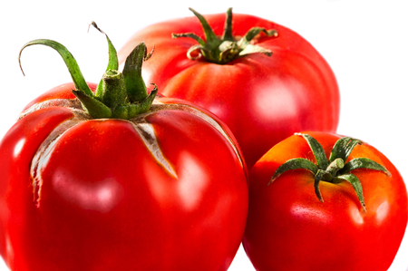 Three tomatoes closeup isolated on white