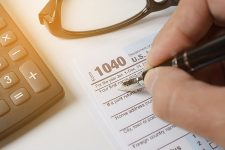 Foto de Man filling US tax form. tax form us business income office hand fill concept - closeup - Imagen libre de derechos