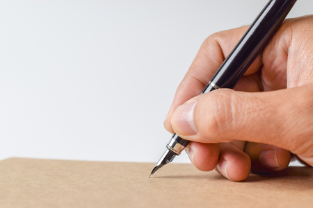 Photo pour Human hand signing on formal paper at the table on white background - Close-up - image libre de droit