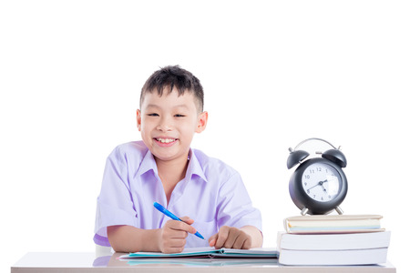 Photo pour young asian schoolboy doing homework over white - image libre de droit