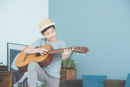 Foto de Young boy playing guitar at home - Imagen libre de derechos
