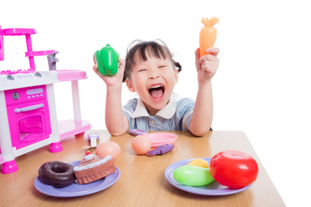 Photo pour Girl playing kitchen toy on table - image libre de droit