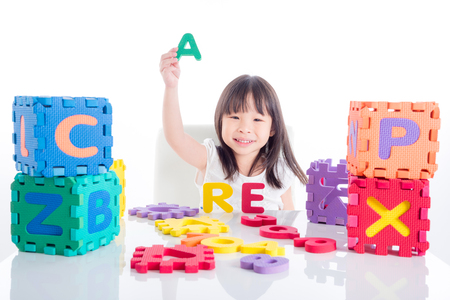 Foto de Little asian girl playing alphabet toy over white background - Imagen libre de derechos