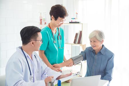 Photo pour Asian doctor and nurse checking senior woman blood pressure at hospital - image libre de droit