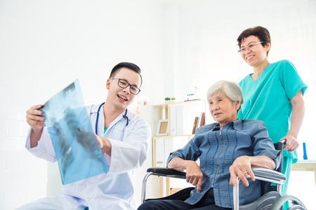 Foto de Asian doctor explain X-ray flim result to his patient in hospital - Imagen libre de derechos