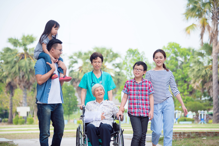 Foto de Senior female patient sitting on wheelchair with her family and nurse in hospital park - Imagen libre de derechos