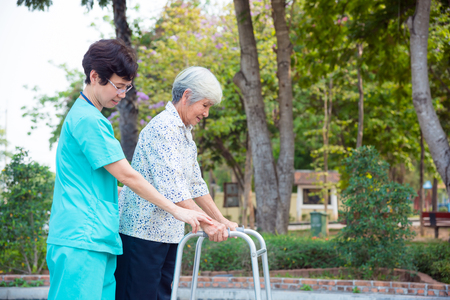 Foto de Asian nurse helping senior female patient walking by walker support - Imagen libre de derechos