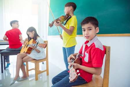 Photo for Young asian boy playing ukulele with friends in music classroom - Royalty Free Image