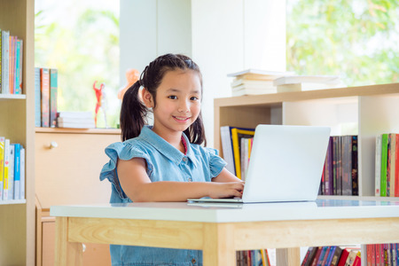 Photo pour Young asian girl using laptopcomputer in library - image libre de droit