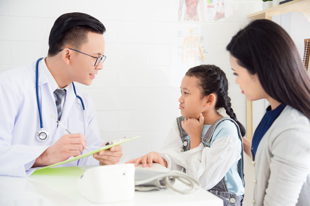 Photo pour Young asian girl with sore throat come to visit doctor with her mother at clinic - image libre de droit
