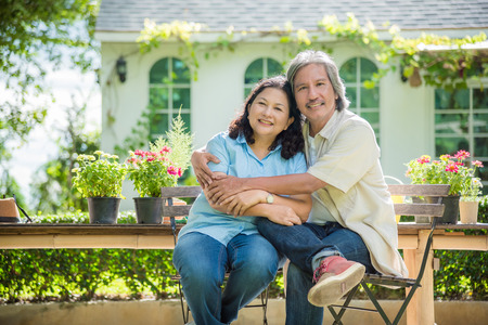 Foto de Retired couple sitting in front of their house and smile happily - Imagen libre de derechos