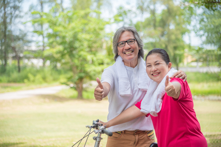 Photo pour Happy asian retired couple showing thumb up and smile in park - image libre de droit