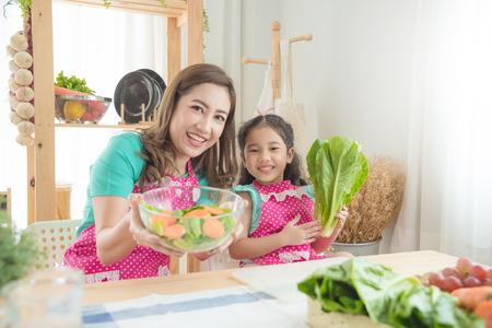 Foto de Beautiful asian mother and daughter wearing pink apron cooking breakfast in the kitchen. - Imagen libre de derechos