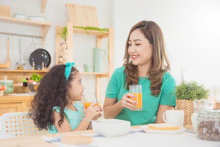 Foto de Beautiful asian mother and daughter having breakfast together at home in the morning - Imagen libre de derechos
