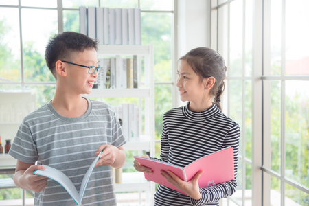 Photo for Young asian boy and girl talking and smiling in classroom - Royalty Free Image
