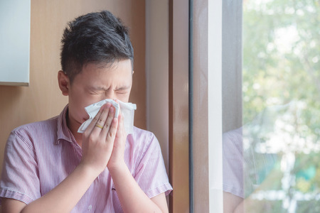 Photo for Sick asian boy blowing nose into tissue, Unhealthy child suffering from running nose or sneezing and covering his nose and mouth by tissue paper. - Royalty Free Image