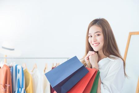 Foto de Beautiful asian woman holding shopping bags and smiles at garments apparel clothing shop. Sale,Shopping concept . - Imagen libre de derechos